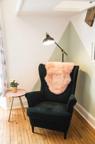 Lamplit green velvet corner armchair with pink sheepskin throw and rose gold side table with flowers